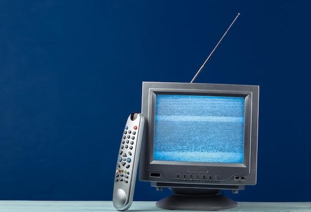 Mini ricevitore antenna tv retrò sul classico blu. vecchio televisore con telecomando.