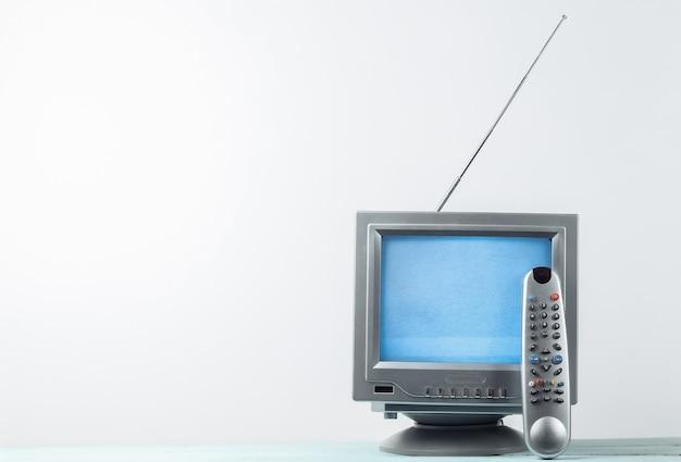 Mini ricevitore antenna tv retrò su un bianco. vecchio televisore con telecomando.