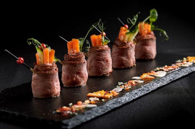 Involtini di mini arrosto di manzo con verdure, su una lastra di ardesia nera, su uno spazio nero