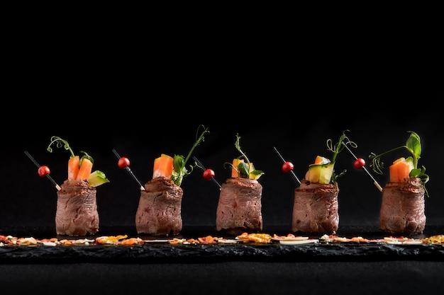 Involtini di mini arrosto di manzo con verdure, su una lastra di ardesia nera, su una parete nera. fusion food concept, low key, copia spazio.