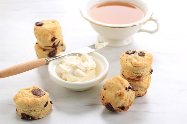 Mini focaccine rotonde con panna rappresa e una tazza di tè, fondo in marmo bianco