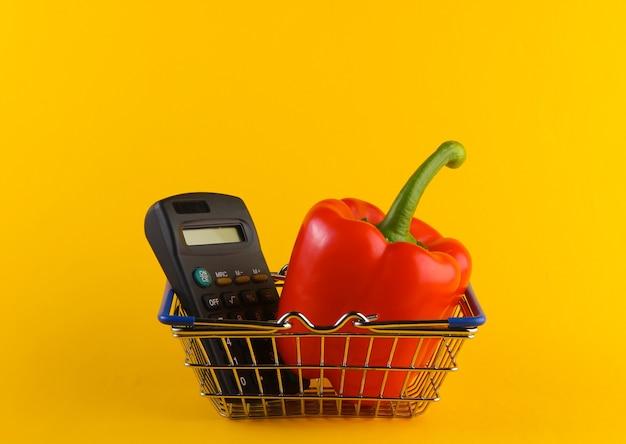 Mini cestino della spesa con peperone e calcolatrice su colore giallo.