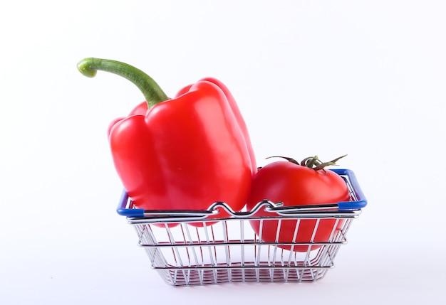 Mini cestino della spesa con peperone rosso e pomodoro su bianco