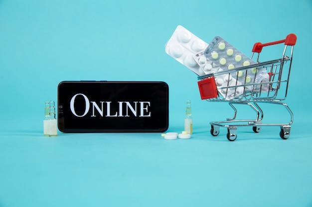 Mini carrello pieno di rimedi omeopatici su sfondo portatile. omeopatia e concetto di acquisto online di internet.