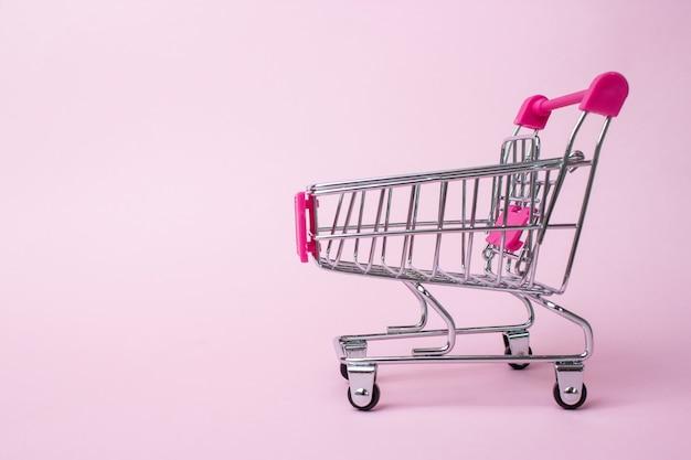 Mini carrello su su sfondo rosa pallido. affari, concetto di e-commerce.