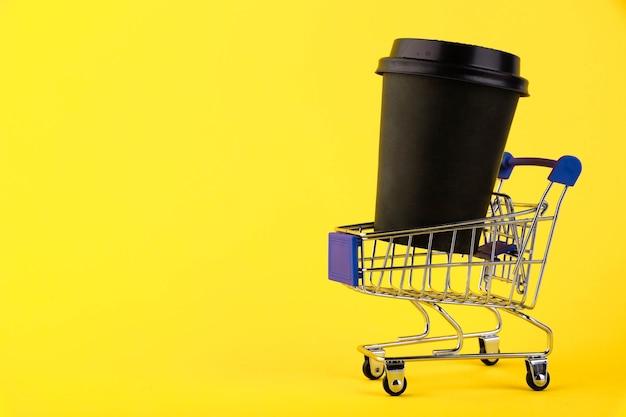 Mini carrello della spesa con un bicchiere di carta da caffè nero su sfondo giallo