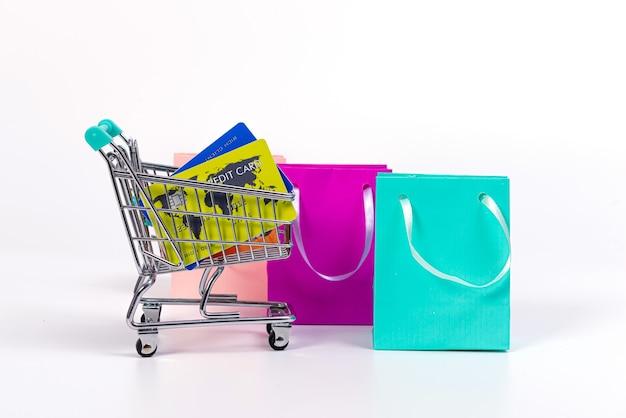 Mini carrello con carte di credito e sacchetti di carta colorati isolati su superficie luminosa