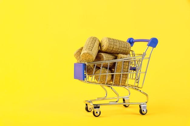 Mini carrello con tappi per vino in legno su sfondo giallo
