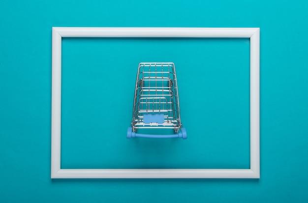 Mini carrello della spesa su superficie blu con cornice bianca
