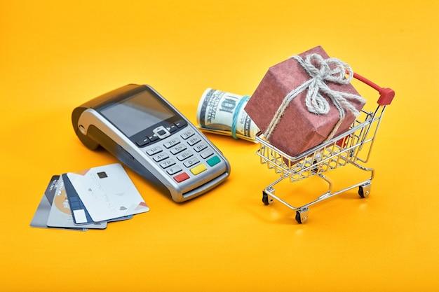 Mini carrello della spesa pieno di scatola regalo, banconote in dollari e carte di credito su giallo