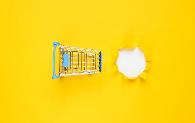 Mini carrello della spesa e un foro strappato in carta gialla. concetto di shopping minimalista
