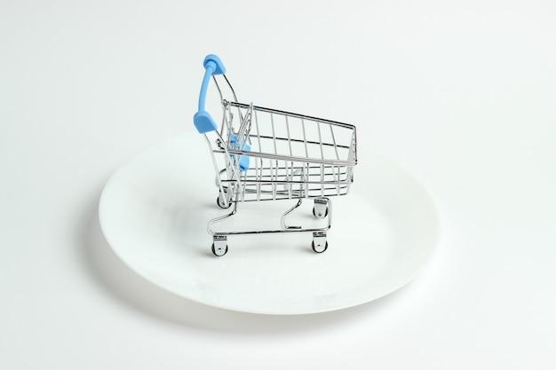 Mini carrello della spesa su un piatto bianco. concetto di consumatore