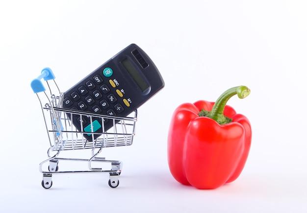 Mini carrello della spesa con peperone e calcolatrice su bianco