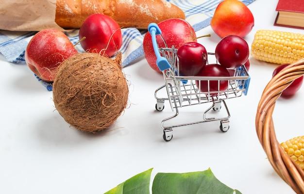 Mini carrello della spesa con frutta e cesto su uno sfondo bianco. foglia di monstera.