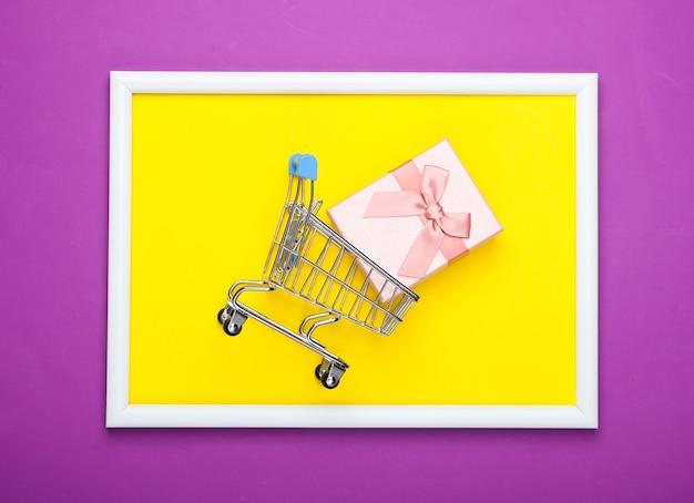 Mini carrello della spesa con scatola regalo su superficie viola con portafoto