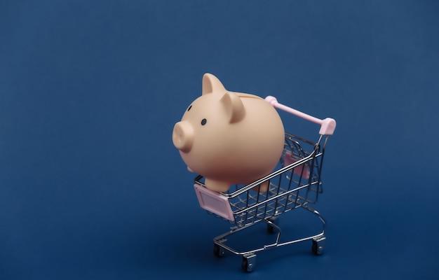 Mini carrello della spesa con salvadanaio su sfondo blu classico