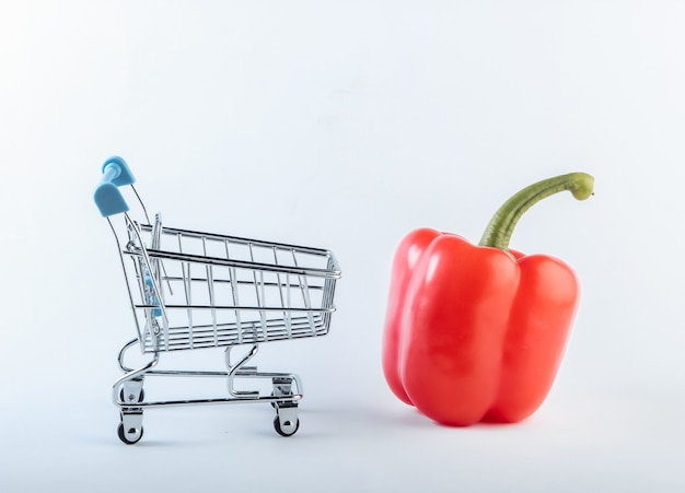 Mini carrello della spesa con peperone rosso su fondo bianco