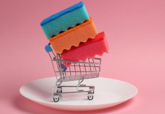 Mini carrello della spesa con spugne per lavare i piatti su un piatto. sfondo rosa pastello
