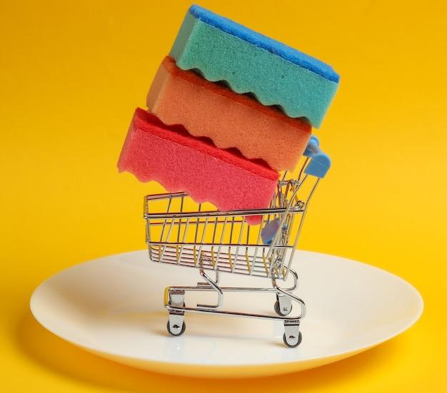Mini carrello della spesa con spugne per lavare i piatti su un piatto. sfondo giallo