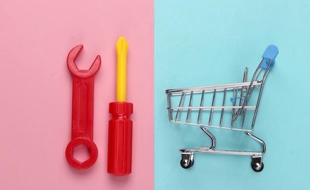 Mini carrello della spesa con attrezzi da lavoro giocattolo su un pastello blu-rosa.