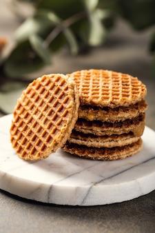 Mini stroopwafel, biscotti syrupwaffles con tazza di tè e rametti di eucalipto su superficie chiara Foto Premium