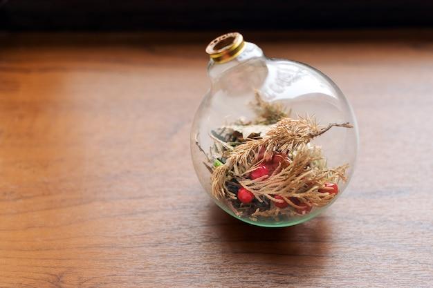 Mini giardino succulento in terrario di vetro su davanzale in legno, piante grasse con sabbia e rocce in scatola di vetro, elementi di decorazione della casa.