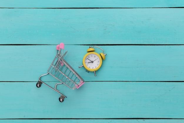 Mini carrello del supermercato e retro sveglia su fondo di legno blu. tempo di acquisti.