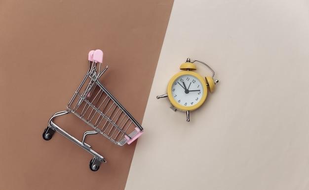 Mini carrello per supermercati e sveglia retrò su sfondo beige marrone.