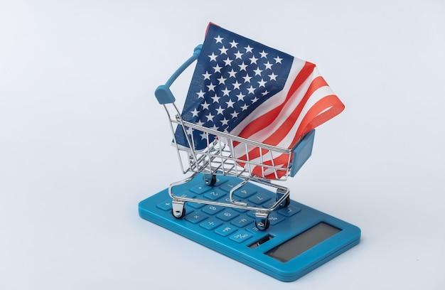 Mini carrello per supermercati con bandiera degli stati uniti, calcolatrice su sfondo bianco. shopping americano