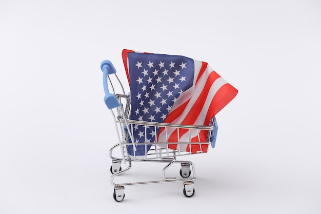 Mini carrello per supermercati con bandiera degli stati uniti su sfondo bianco. shopping americano