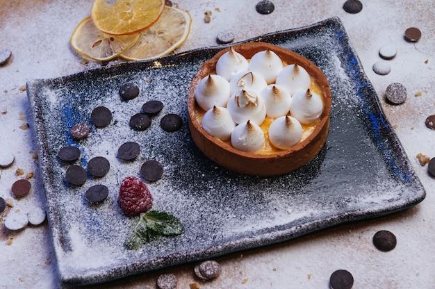 Mini tartelletta con marmellata di frutta e meringa crostata con meringa italiana e crema su piastra nera deserto fatto in casa bella colazione