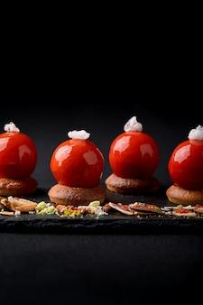 Mini tortine di frutti di bosco smaltate in alto splendidamente disposte su un piatto nero. moderna mousse di tortino festivo da dessert e glassa a specchio rossa a forma di cappello di babbo natale.