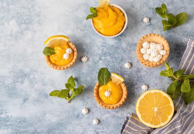 Mini crostate con lemon curd, mini meringa, fette di limone e menta su fondo blu in cemento