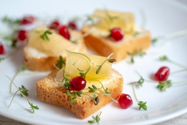 Mini toast con burro, formaggio e micro verdure di crescione su un piatto bianco. concetto di colazione, Foto Premium