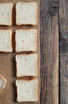 Mini toast disposti verticalmente in fila su carta pergamena su un vecchio tavolo in legno vista