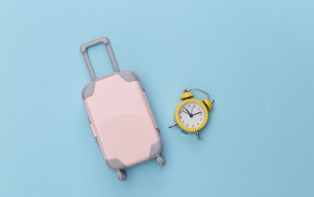 Mini bagaglio da viaggio e sveglia su sfondo blu pastello.