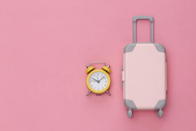 Mini bagaglio da viaggio e sveglia su sfondo rosa pastello. . copia spazio