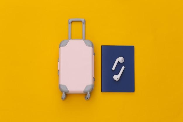 Mini bagaglio da viaggio e cuffie wireless, passaporto su sfondo giallo.