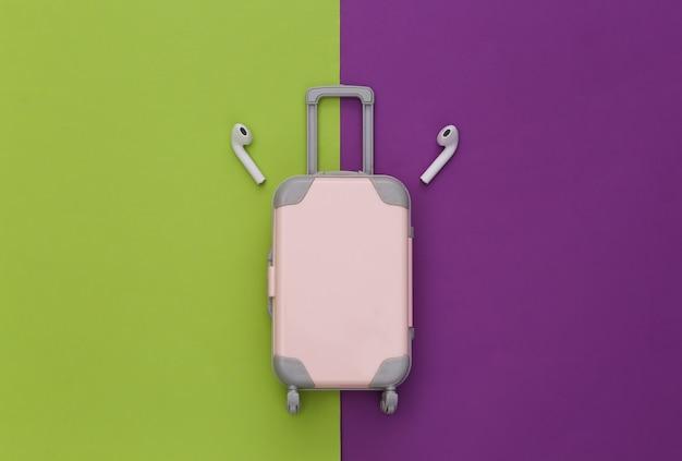 Mini bagaglio da viaggio e cuffie wireless su sfondo viola-verde.