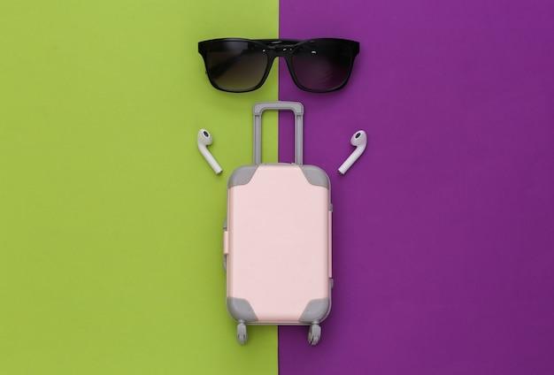 Mini bagaglio da viaggio e cuffie wireless, occhiali da sole su sfondo viola-verde.