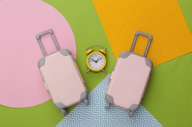 Mini bagagli da viaggio e sveglia su sfondo di carta colorata creativa. tempo di viaggiare.