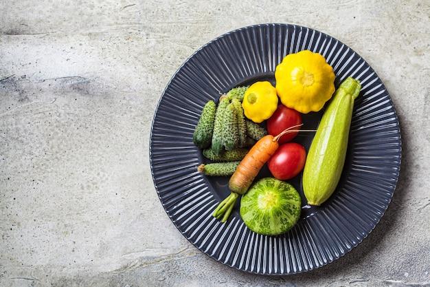 Mini concetto di verdure. mini zucchine, pomodori, cetrioli, zucca e carote su un piatto scuro.