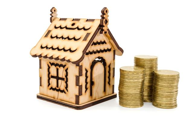 Mini casa in legno con pile di monete isolate su bianco