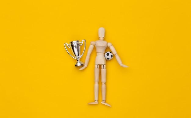 Mini burattino di legno che tiene pallone da calcio e coppa del campionato su sfondo giallo