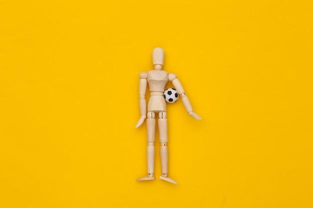 Mini burattino di legno che tiene un pallone da calcio su sfondo giallo