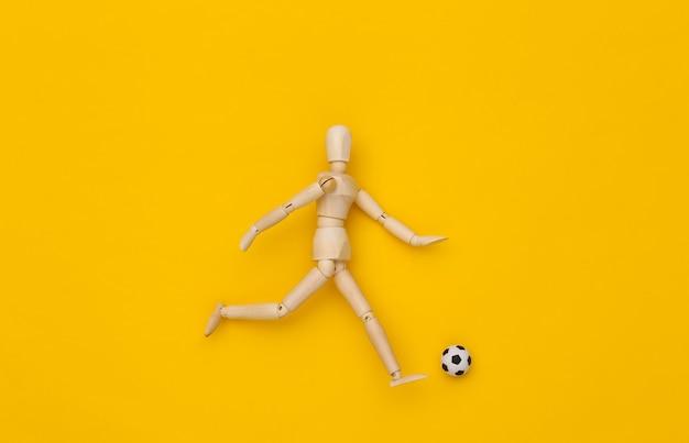 Mini burattino di legno che corre con un pallone da calcio su sfondo giallo