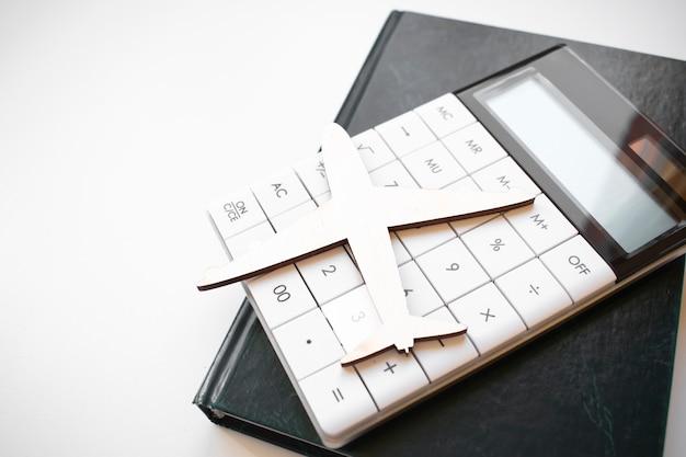 Modello di aeroplano in miniatura con calcolatrice per budget di viaggio, concetto di costi o spese