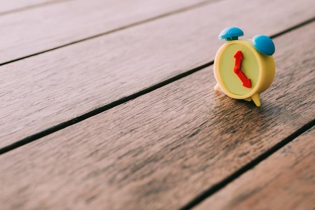 Annata miniatura della sveglia sul tono di colore d'annata della tavola di legno