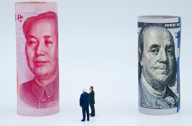 Uomini d'affari in miniatura con banconote in dollari usa e cina yuan