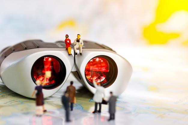 Gente di affari miniatura che si siede sopra il binocolo per trovare la gente da lavorare, concetto di assunzione.